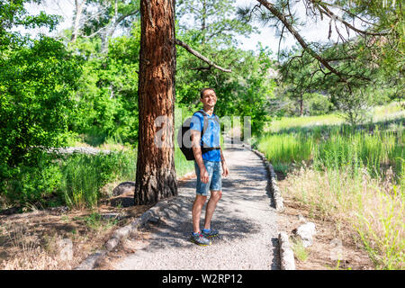 Scenery of tree and path with man hiking at Main Loop trail in Bandelier National Monument in New Mexico during summer in Los Alamos - Stock Image