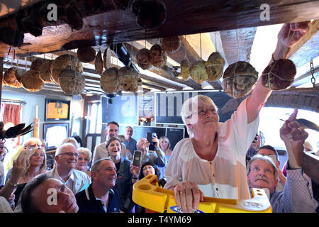 Pub employee Margaret Utteridge, 74, who has worked at The Bell Inn, High Road, Horndon-on-the Hill, Essex since 1984, hangs a hot cross bun from a beam which has been a tradition at the inn since 1906. - Stock Image