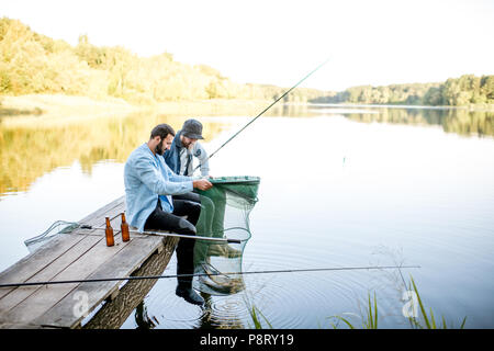 Two happy male friends looking at the fishing net with fish during the fishing on the lake - Stock Image