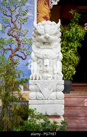 Statue of lion-dog in the front garden of Phap Bao Buddhist temple in the town of Hoi An, Central Vietnam. - Stock Image