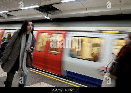 London underground tube train in motion and female passenger walking along platform at Brixton station in South London UK  KATHY DEWITT - Stock Image