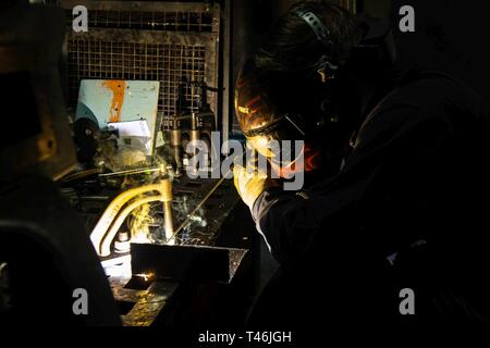 Atlantic Ocean (Mar. 13, 2019) Hull Technician 3rd Class Hardy William welds together two pieces of metal on the Arleigh Burke-class guided-missile destroyer USS Jason Dunham (DDG 109). Hull technicians are responsible for the welding and plumbing onboard the ship. - Stock Image