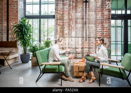 Business people sitting on the green sofas during a lunch at the beautiful loft interior on the brick wall background - Stock Image