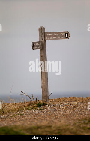 Wooden signpost on a Norfolk beach indicating the Norfolk coastal path and Weybourne - Stock Image