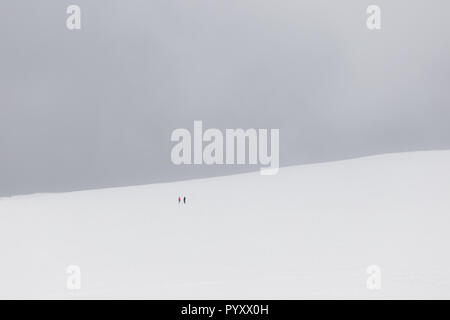 A very minimalistic view of two distant people over a mountain covered by snow - Stock Image