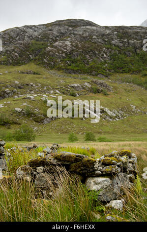 Part of the remains of an abandoned shiel provide the foreground for an image of the rocky Glen Nevis - Stock Image
