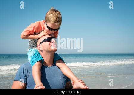 Father with his young son on shoulders enjoying family day at the beach - Stock Image