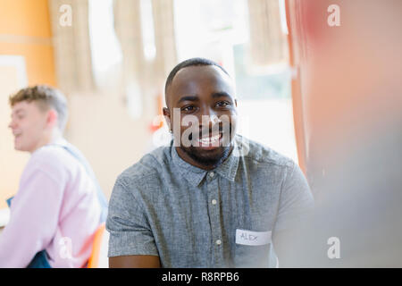 Smiling young man listening in group therapy - Stock Image