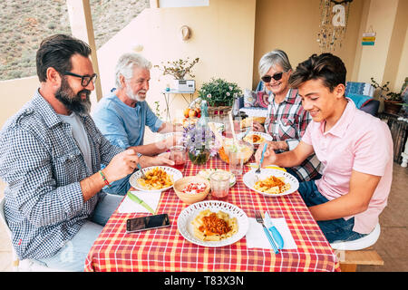 Family people outdoor lunch together on a red table - mixed ages generations enjoy and have fun with italian pasta on the terrace at home - father gra - Stock Image