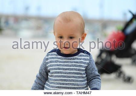 Adorable Blond Baby Boy Wearing A Blue And White Sweater On The Sandy Beach, Close Up Portrait - Stock Image