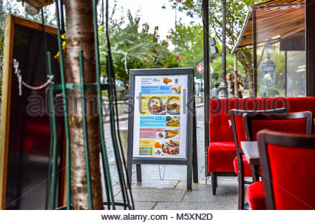 A sidewalk cafe in Paris France sits empty with a tourist menu board in front advertising crepes, breakfast and - Stock Image