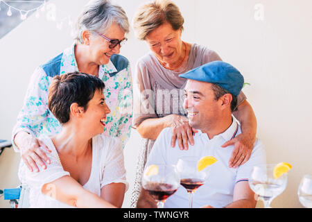 Family people cheerful portrait with mothers and son hugging and enjoying the friendship - mixed generations from old senior to adults together drinki - Stock Image