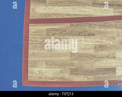 Red playfield line in blue square. Marks on fooden floor of sports gymnasium. Ground colorful marking lines - Stock Image