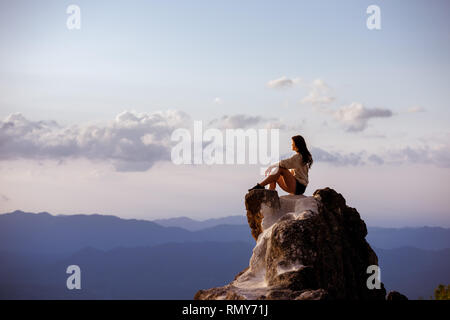Beautiful girl sits on big rock at sunset time and relax. Space for text - Stock Image