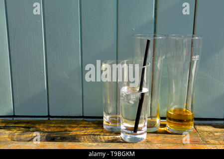 Part empty drinks glasses casting shadows - Stock Image