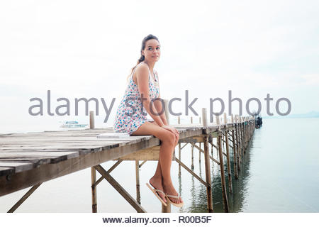 Young woman wearing floral dress sitting on pier - Stock Image