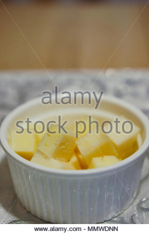 Gouda cheese blocks in a white bowl in soft focus - Stock Image