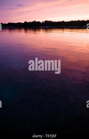 Pink hues of sunset reflecting on Lake Michigan - Stock Image
