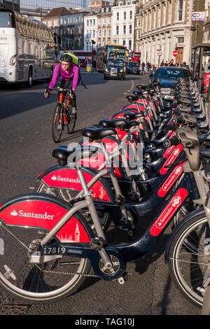 London Cyclist TFL Santander sponsored London red rental hire bikes in Southwark Street. Commuter cyclist wearing helmet riding by the bike terminal docking station with traffic behind. Transport for London Southwark London UK - Stock Image