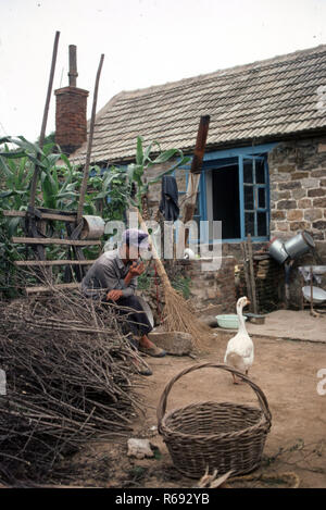 North China 1980 Commune in Waoning Province where farmer rests smoking  by stone house - Stock Image