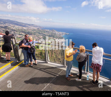 Madeira, Portugal - November 02, 2018: Tourists at Cabo Girao Skywalk viewpoint. Funchal, the capital of Madeira, Portugal, in the background. - Stock Image