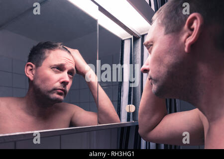 Mid adult caucasian man looking at himself scrutinising his face and receding hairline in the bathroom mirror - Stock Image