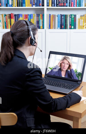 Psychologist in her office in front of her computer, talking to a extremely stressed woman during a live video call or chat, online counseling concept - Stock Image