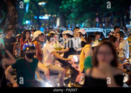 Motion blurred night shot of mopeds in busy street in Hanoi, Vietnam. The seemingly chaotic traffic scares tourists but is commonplace for locals. - Stock Image