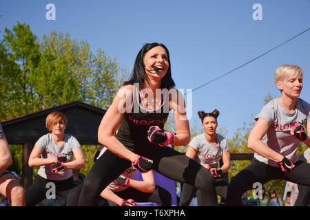 Nis, Serbia - April 20, 2019 Female group practicing pose under control of female Piloxing teacher outdoors - Stock Image