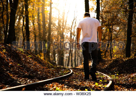 Man walking on train rails on fall with leaves on the ground during sunset - Stock Image