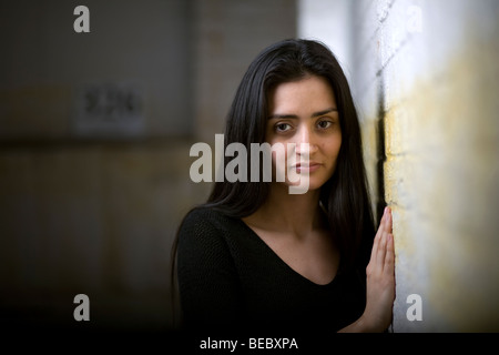 An attractive Latin or Hispanic female leaning against a wall. - Stock Image