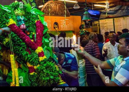 Worshipers Offering Prayers to Hindu God Hanuman,  Decorated with Garlands and Offerings, Sree Veera Hanuman Temple, Kuala Lumpur, Malaysia. - Stock Image