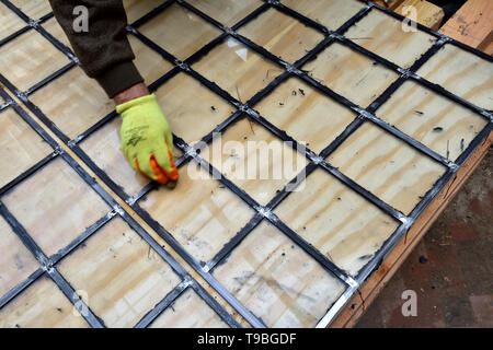 Craftsman cleans lead came on leaded glass window pane before finishing grouting - Stock Image