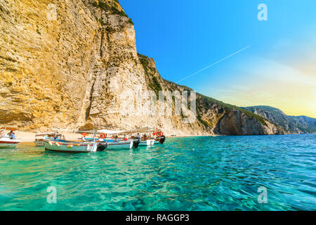 Boats line up at the shoreline in the clear waters off the sandy Paradise Beach or Chomi Beach on a sunny day in Corfu Greece. - Stock Image