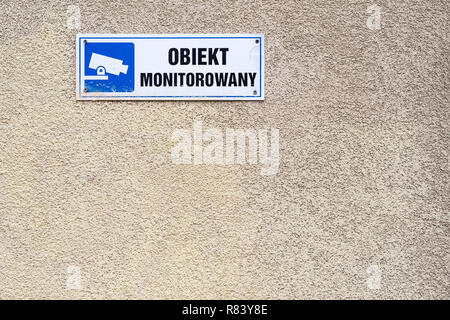 under video surveillance text in Polish, blue CCTV symbol on the wall in Warsaw, Poland - Stock Image