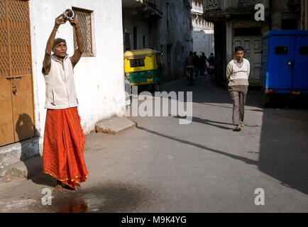 Man performing morning rituals offering water to God Sun in Ahmedabad city of India. Recently recognized as world Heritage city. - Stock Image