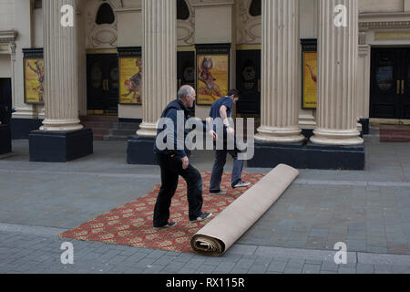 Carpet fitters unroll a new carpet in the street for the interior of the Lyceum Theatre on Wellington Street, on 5th March 2019, in London, England. - Stock Image