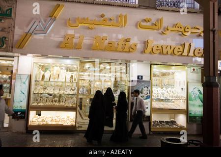 Dubai Deira gold market gold souq veiled women in front of Kranz Jewels - Stock Image