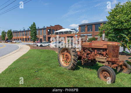 HICKORY, NORTH CAROLINA,  USA-9/1/18:  Hollar Mill, a renovated mill building, containing specialty stores and shops, with antique Farmall tractor. - Stock Image