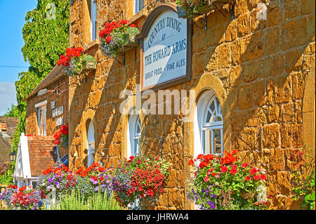 Colourful hanging baskets on the front of a Cotswold stone public house, in the Warwickshire village of Ilmington - Stock Image