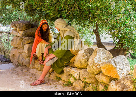 A young men and woman in period costume in the open air museum of Nazareth Village Israel. This site provides a look at life in ancient Israel - Stock Image