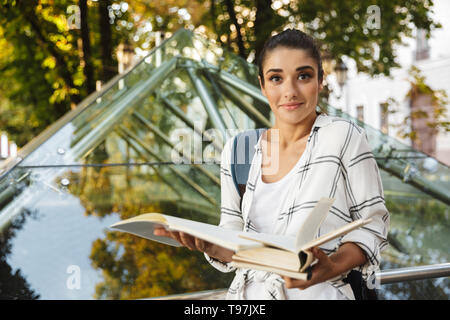 Pretty girl student reading a book while standing at the park - Stock Image
