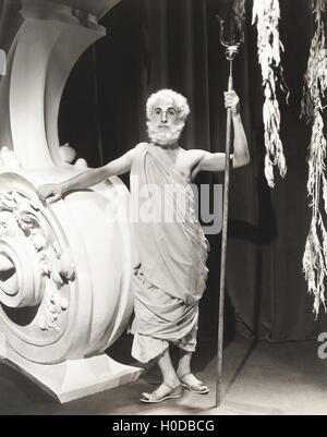 Man in toga holding trident - Stock Image
