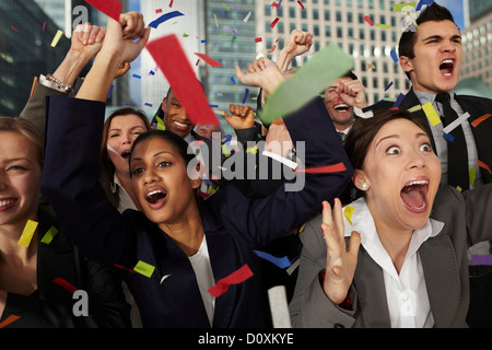 Businesspeople cheering as ticker tape falls - Stock Image