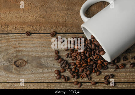 A blank customizable coffee mug on a wooden table with coffee beans and copy space. - Stock Image