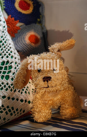 A  plush dog is sitting on a sofa. - Stock Image