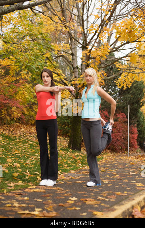 Two young women stretching during autumn. - Stock Image