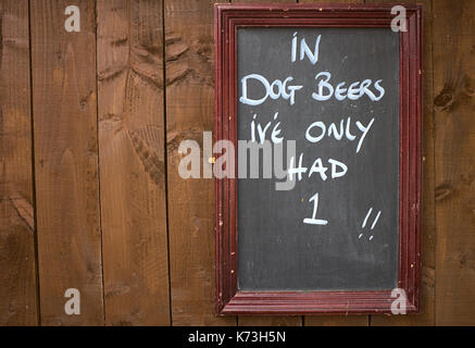 Humorous sign on a wooden wall or fence in a pub, Yorkshire, United Kingdom. - Stock Image