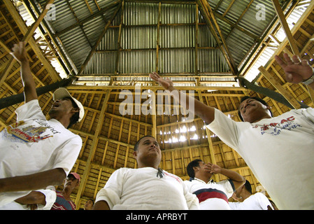 Filipinos negotiate their bets before a cockfight at a rural cockhouse in Oriental Mindoro, Philippines. - Stock Image