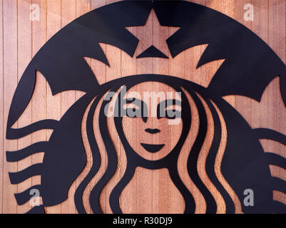 A large Starbucks Coffee Siren brand design on a store front in Birmingham, UK.the design is in black and placed onto a wooden background - Stock Image
